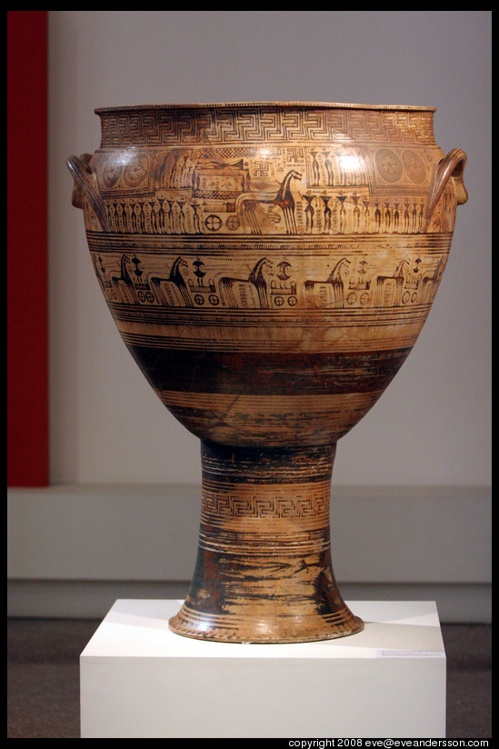 Color photo shows a Greek krater (large vase used for mixing wine). It is decorated with a variety of geometric patterns.