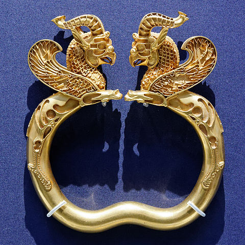 Photo of a gold cuff-style bracelet with two griffin heads.