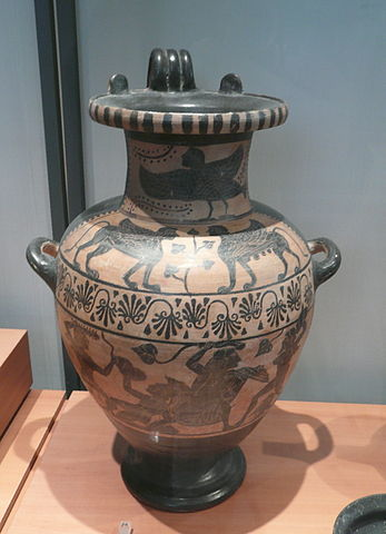 This is a photo of a water carrying vessel with three handles. It is decorated with a with black-figure paintings of mythological creatures.