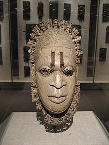 The mask features a serene face of the queen mother wearing a headdress as well as scarification highlighted by iron inlay on the forehead, all framed by an openwork tiara and collar.