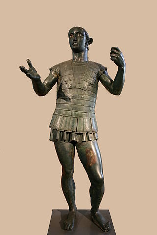 This is a photo of the statue the Mars of Todi. This bronze statue depicts a male Etruscan warrior wearing intricate body armor. His pose places most of his weight on one foot so that his shoulders and arms twist off-axis from his hips. His left hand is closed, as if gripping an object. His right hand is outstretched as if offering an object.