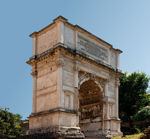 This is a photograph of the Arch of Titus. It shows both the fluted and unfluted columns of the arch, the inscription, and a partial view of the soffits (underside of the arch) which are decorated with a relief of Titus.