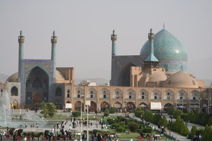 This photo shows the Imperial Mosque, Isfahan, Iran. It is panorama that displays the architecture, including a large blue-domed mosque.