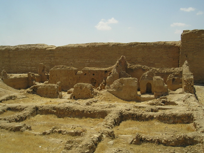 This is a photo of the remains of the Synagogue at Dura-Europos. It shows the ruins of the courtyard, western porch and prayer hall. The remains resemble a sand castle in color and shape.