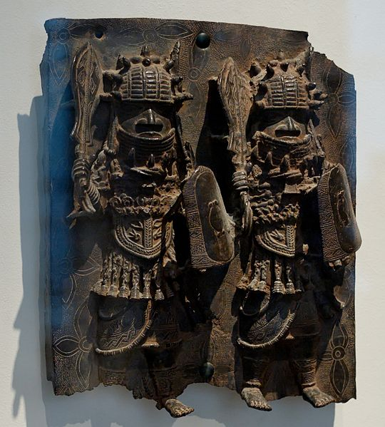 This sculpture depicts two elaborately carved figures wearing armor and holding weapons.