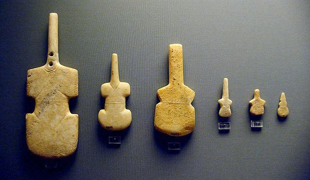 This is a color photograph of six violin-shaped female figurines (circa 3300–2700 BCE). These flat, abstracted figurines of the female body provide one example of how its representation evolved in Cycladic art.