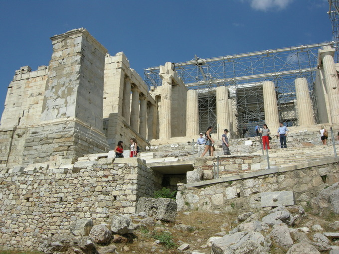 This is a color photo of the Propylaea as it stands today, in the Acropolis at Athens. The photo shows the steps leading up to a six-columned Doric façade.
