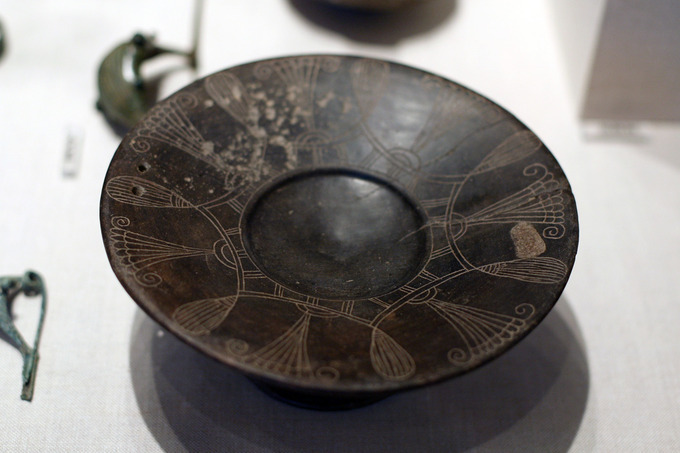 This is a photo of a bucchero Etruscan plate. Its rim is decorated with an abstract design.