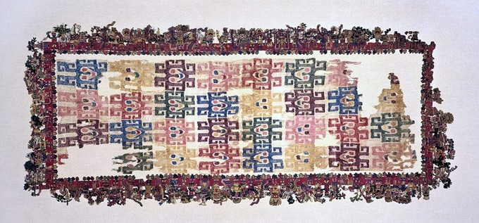 Many figures are embroidered around the border of the textile, and inside the border are colorful geometric designs.