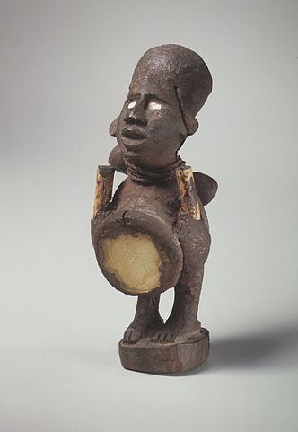A dark colored carving of a human-like figure with a large head and a protruding abdomen painted a light color.