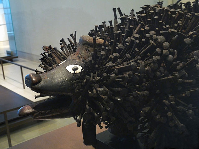 A figure of an animal with its mouth open, covered in nails.