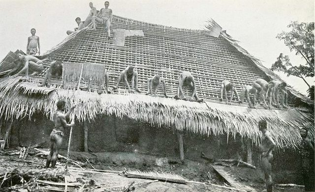 A black and white photo of a group of men working on the roof of a Mbari house.