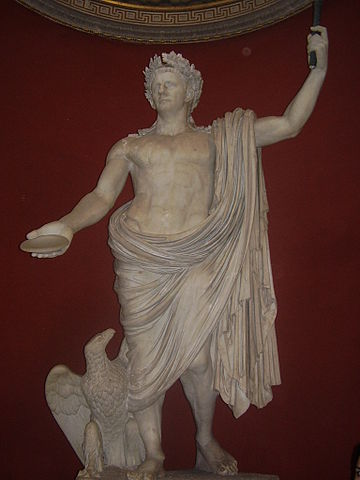 This photo shows a statue of Claudius as Jupiter. Claudius wears a laurel crown and a toga, which reveals his idealized chest and torso. An eagle-like bird rests by his foot.