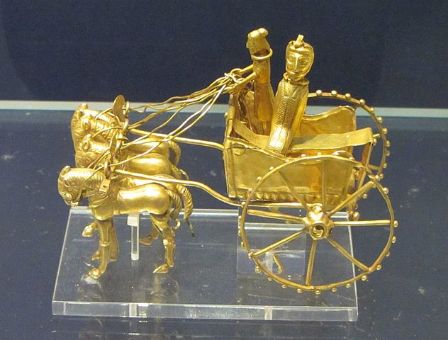 Photo depicts gold figurine of a chariot pulled by three horses. Inside the chariot are a driver and passenger.