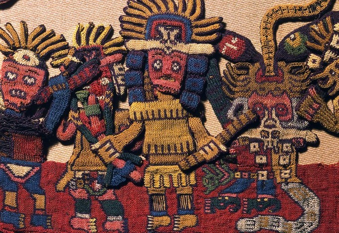 A close-up of a detailed and colorful figure on the border of the textile. He is wearing a headdress and is holding an object in each hand.