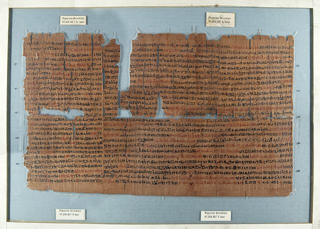 Photograph depicts the Brooklyn Papyrus inside of museum display. It is a ragged-edged, torn piece of papyrus with red and black script.