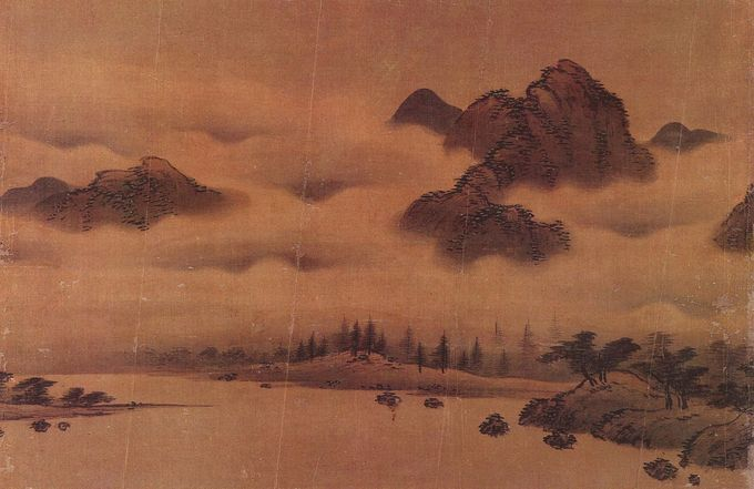 Landscape with a body of water surrounded by low banks. In the background are large peaks emerging from thick fog.