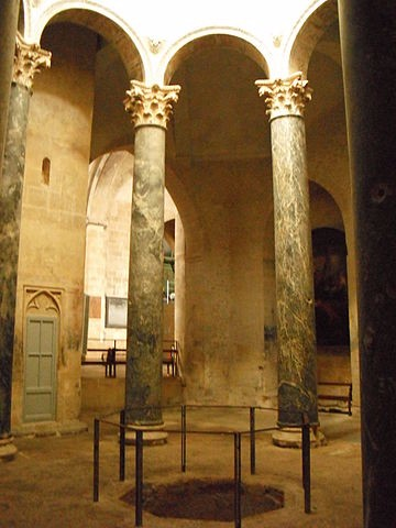 The interior of the Baptistery with two columns and a hole in the floor.