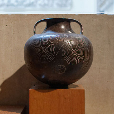 This is a photo of Etruscan pottery. It is a round vase with a thin neck and handles. It is decorated with two spirals and a stylized bird.