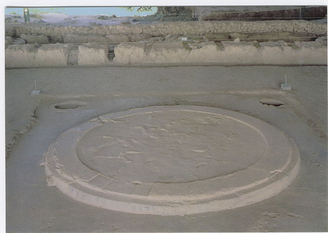 Photo depicts the hearth found in the megaron. It is a raised circular area on the floor, surrounded by four holes leftover from wooden columns.