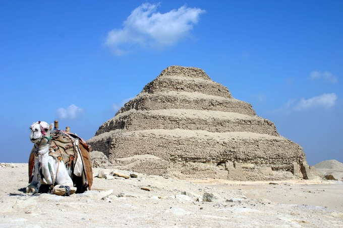 Photograph depicts tiered mud brick pyramid against a blue sky. In the bottom left corner of the shot, there is a camel lying down.