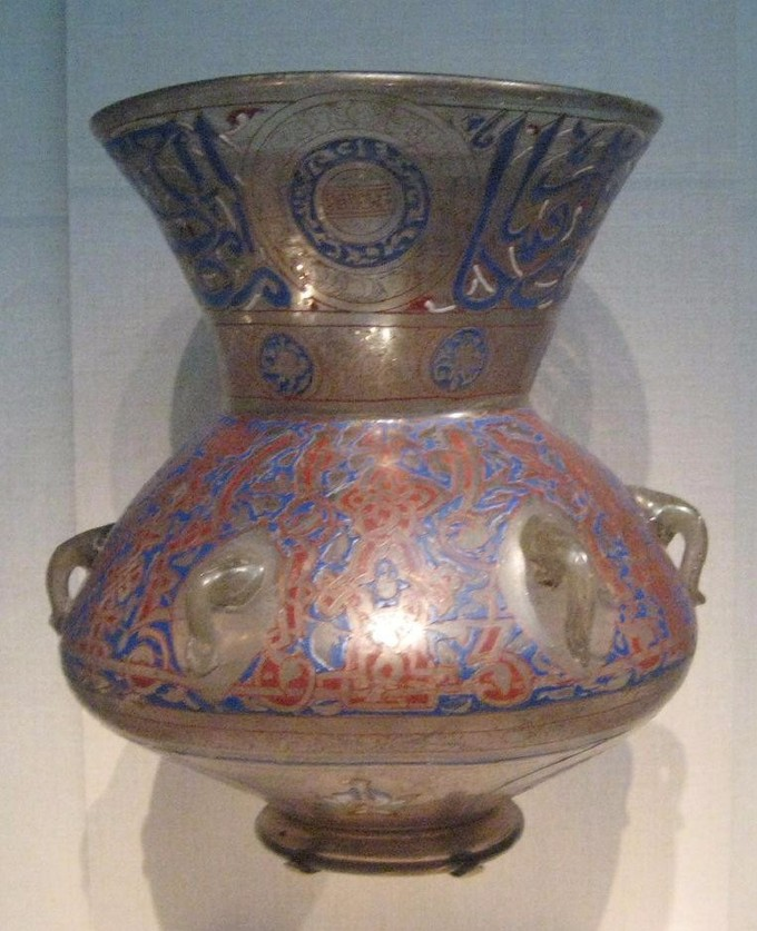 This is a photo of a glass mosque lamp, which has a large round bulbous body rising to a narrower waist, above which the top section is flared. It is bronze-colored decorated with red and blue arabesques.
