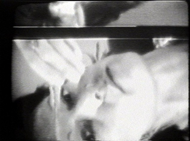 This still from the video shows a woman's face staring at the camera.