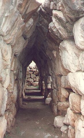 Photo depicts the stone walls that form the archway of the corbel vault in Tiryns, Greece.