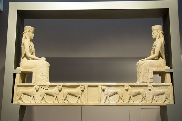 Photo of a marble lintel with a seated woman (possibly a goddess or royalty) on either side. The horizontal support across the bottom features a repeating pattern of a sphinx or other similar animal.