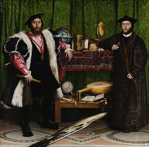 Two men stand on either side of a table that has many objects on it.