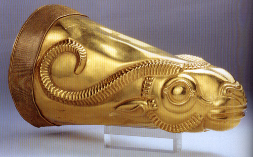 Photo depicts a gold cone-shaped drinking cup with a relief of a bull's face and horns.