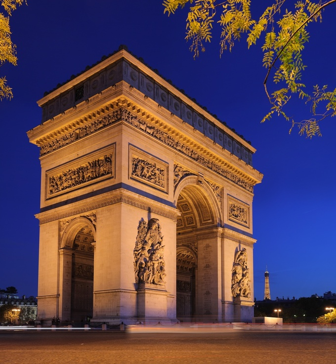 Photo of the Arc de Triomphe lit up at night. There are two enormous archways leading inside, and it is intricately decorated on the outside.