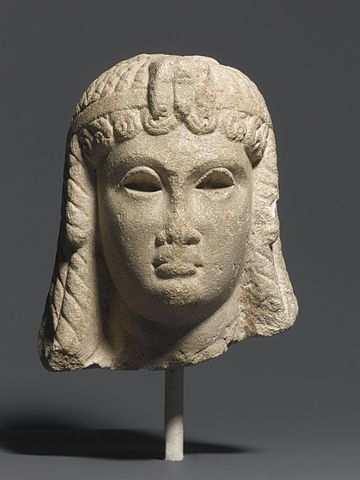 Sculpture depicts the head of a woman with shoulder-length hair wearing a headpiece.