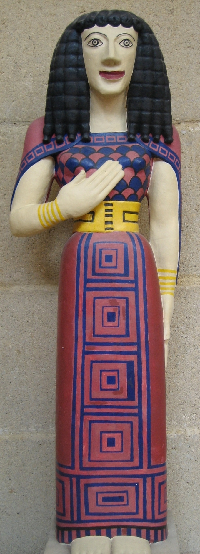 This is a color photo of reconstruction of Lady of Auxerre. The statue's hair, face, and dress have been painted. Her hair is dark brown, her lips are bright red, and the dress is decorated with a square geometric pattern.