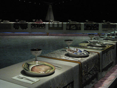 Picture of a section of the installation. Differently designed plates are set with silverware and wine chalices.