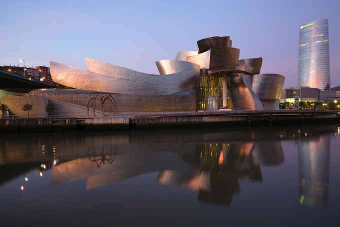 Image of the exterior of the Bilbao Guggenheim. The giant, titanium curves appear random.