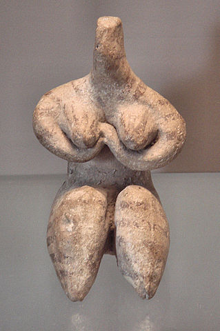 Statue depicts a nude woman with round breasts and plump thighs. The statue has no head.