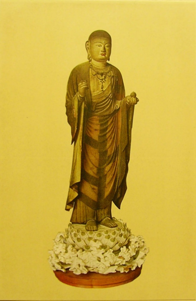 The buddha is depicted in a golden color, standing on an elaborately decorated base.