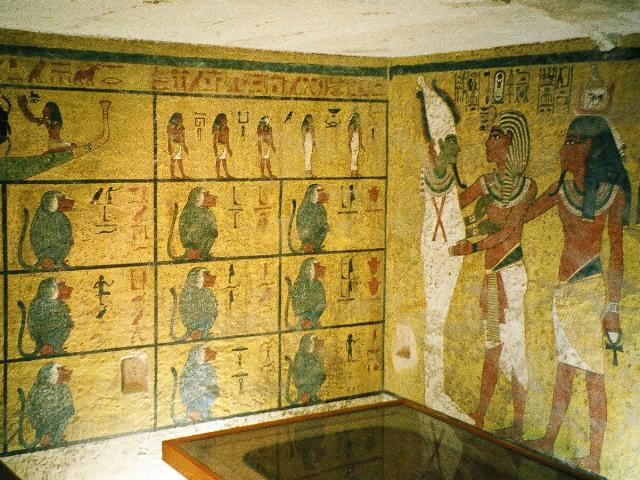 Photograph of Tutankhamun's burial chamber walls. Photo features the portion of the north wall decorated with a mural of King Tut embracing Osiris, clad in a white robe and hat. The western wall is decorated with illustrations that represent Egyptian beliefs about the afterlife, including twelve baboons, a boat, a beetle, and an assortment of gods.