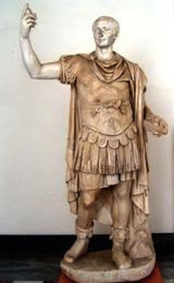 This is a photo of a full-length sculpture of Tiberius in military clothing, including a breast plate. He stands in contrapposto pose and raises his left arm, at a 90-degree angle.