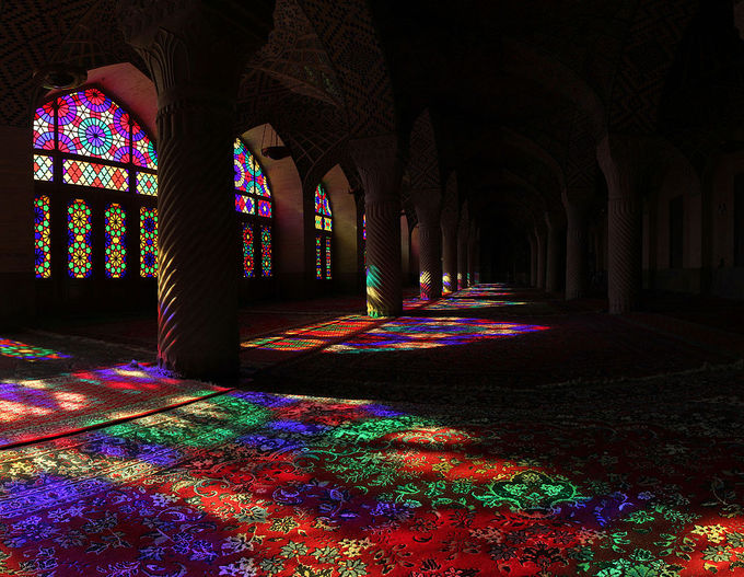 The sun shines through stained glass windows at the Nasir ol Molk Mosque located in Shiraz, Iran.