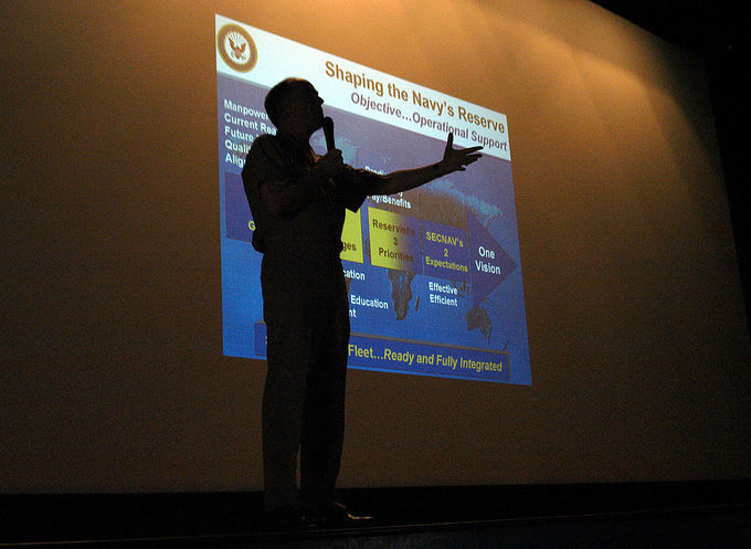 Commander Naval Reserve Force, Vice Adm. John G. Cotton, stands in front of a PowerPoint presentation at the Naval Station North Island's theater.