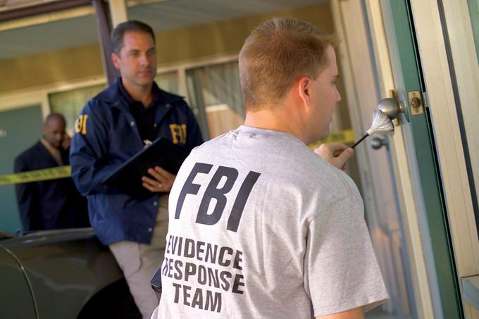 Members of an FBI response team check a crime scene for evidence.