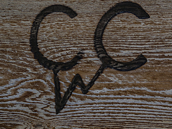 A cattle brand burned onto a piece of wood.