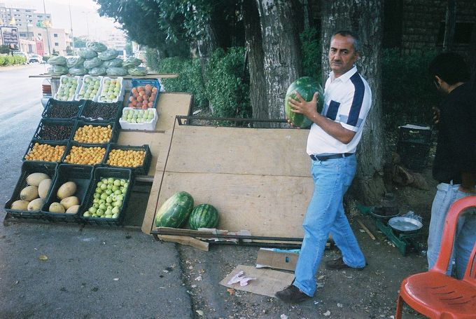 A man buys a watermelon at a fruit stand in Lebanon.