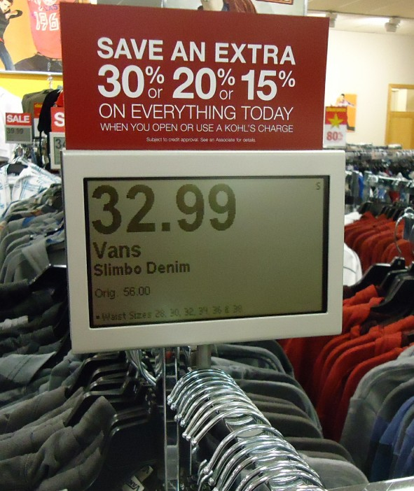 An electronic price display on a clothes stand at a retail store.