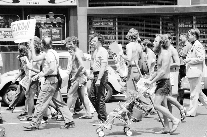 A group of white men, some holding signs, marching down a NYC street.