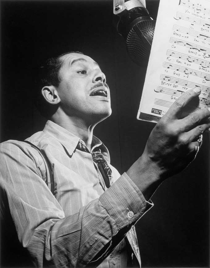 Portrait of Cab Calloway singing into a microphone while holding sheet music.