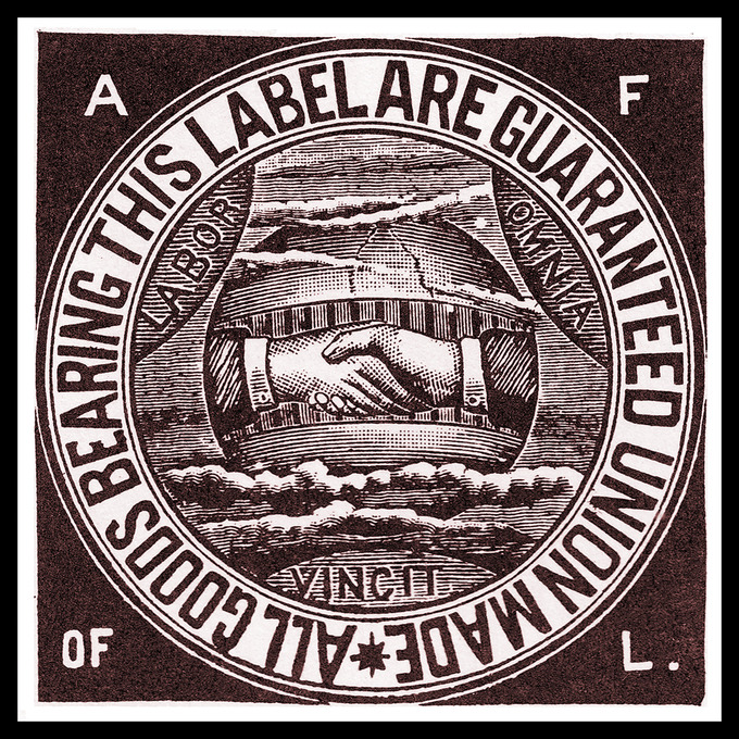 "At its center, the union label shows two hands shaking. The hands are surrounded by the Latin phrase ""Labor Omnia Vincit,"" which translates to ""Work conquers all."" The words ""All Goods Bearing This Label Are Guaranteed Union Made"" wrap around the outside of the label."