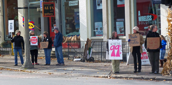 "Occupy protesters with ""We are the 99%"" signs on a sidewalk in Bennington, VT."